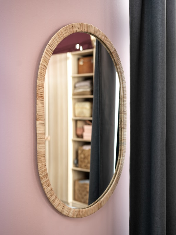 Specchio ovale su parete rosa.