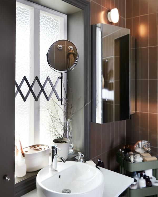 Spegel med utdragbar arm som dragits ut över ett tvättställ, skåp med spegeldörr samt en grågrön rullvagn.