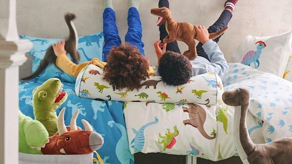 spelende kinderen op het bed samen met heleboel dinosaurusknuffels