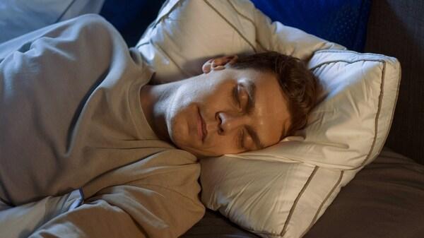 Spiaci muž s hlavou na vankúši.