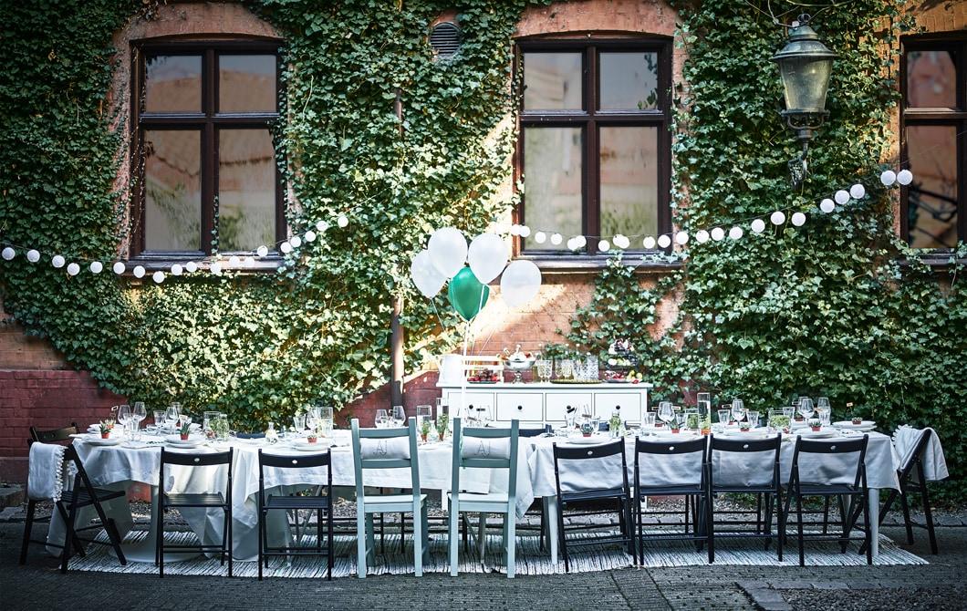 Spisebord dækket op til bryllup står i en baggård.