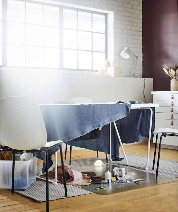 Spisebord i en stue med et stykke stof, der hænger ud over bordets kanter, og som bruges som improviseret arbejdsbord til tegninger osv.