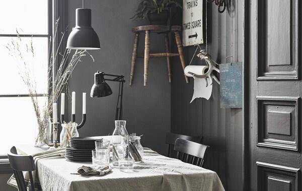 Spisebord med en hørdug i et moderne, rustikt køkken med personlig pynt hængende på væggen