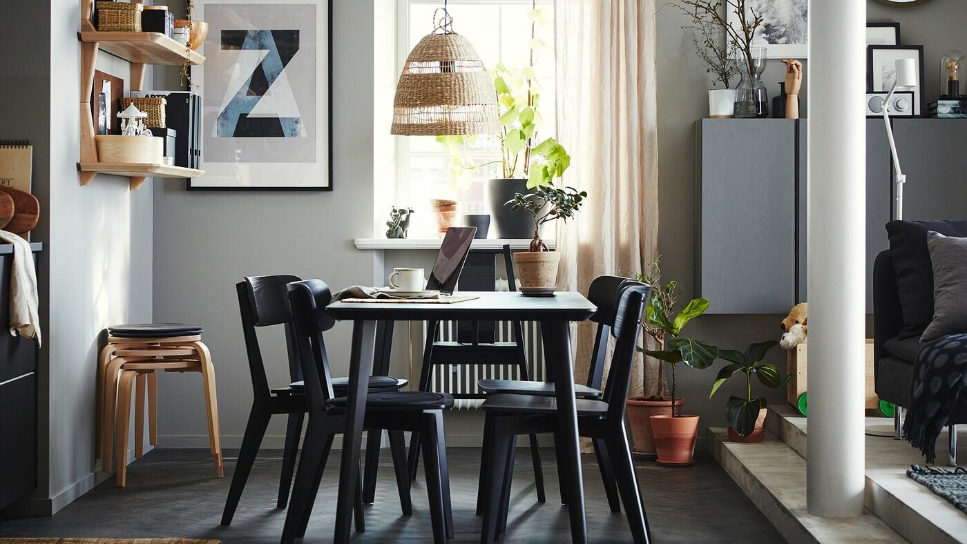 Spiseområde med et bord, 4 stole og en sort højstol, åbne hylder af asketræsfiner, 4 taburetter og beige gardiner.