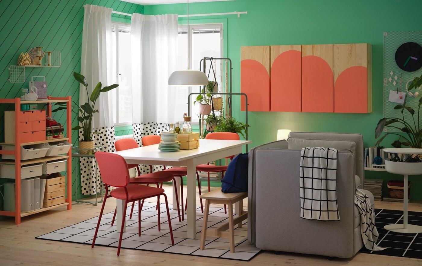 Spiseplass med hvitt bord, røde stoler og grå sofa samt skap og hylleseksjon malt i korallfarge.