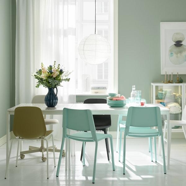 Spiseplass med hvitt MELLTORP bord, hvit REGOLIT lampe og ulike stoler.