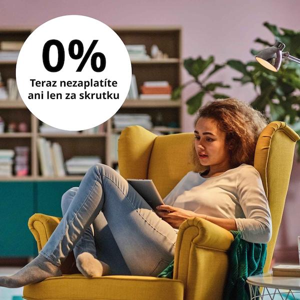 Splátkový predaj -žena sedí v žltom kresle a listuje si brožúrou.