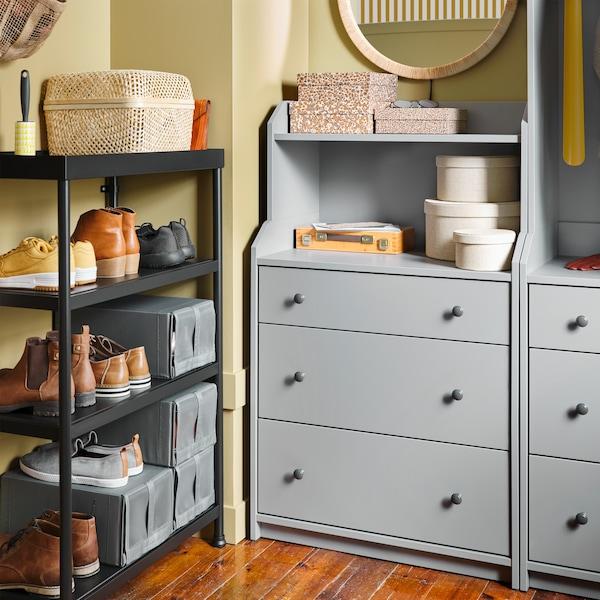Spojene police s cipelama i kutijama za cipele, zidno ogledalo i siva kombinacija za odlaganje s fiokama i policama.