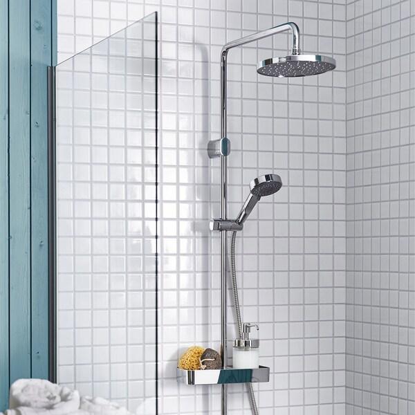 Sprcha BROGRUND v koupelně s bílými obklady, zobrazující hlavovou i ruční sprchovou hlavici.