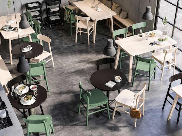 Square and round tables in a café space, all with RÖNNINGE chairs. Large HEKTAR pendant lamps hang from the ceiling.