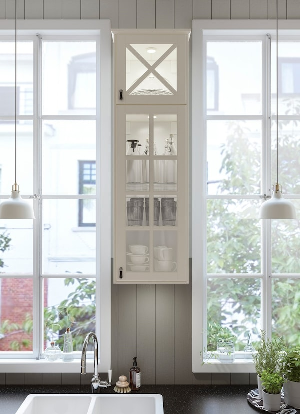 Squeeze an IKEA BODBYN white kitchen cabinet in between a window or into your small kitchen; its vitrine glass doors let you see all your glassware.
