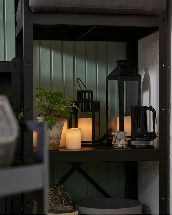 Srednji odeljak spojenih polica u uglu sobe, polica dopola napunjena različitim LED sijalicama, i biljka.