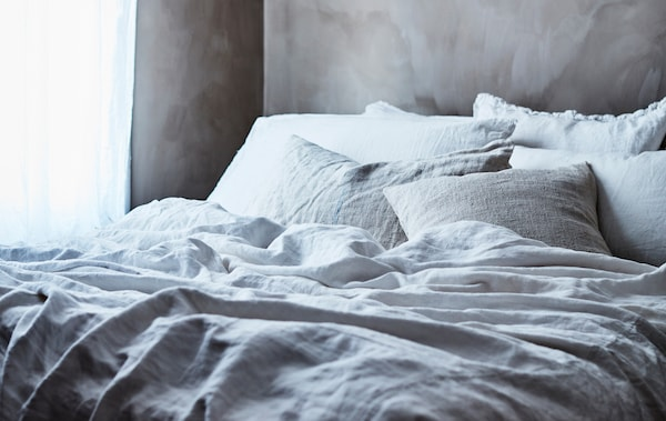 سرير عليه طبقات من مفروشات السرير الرمادي والأبيض.