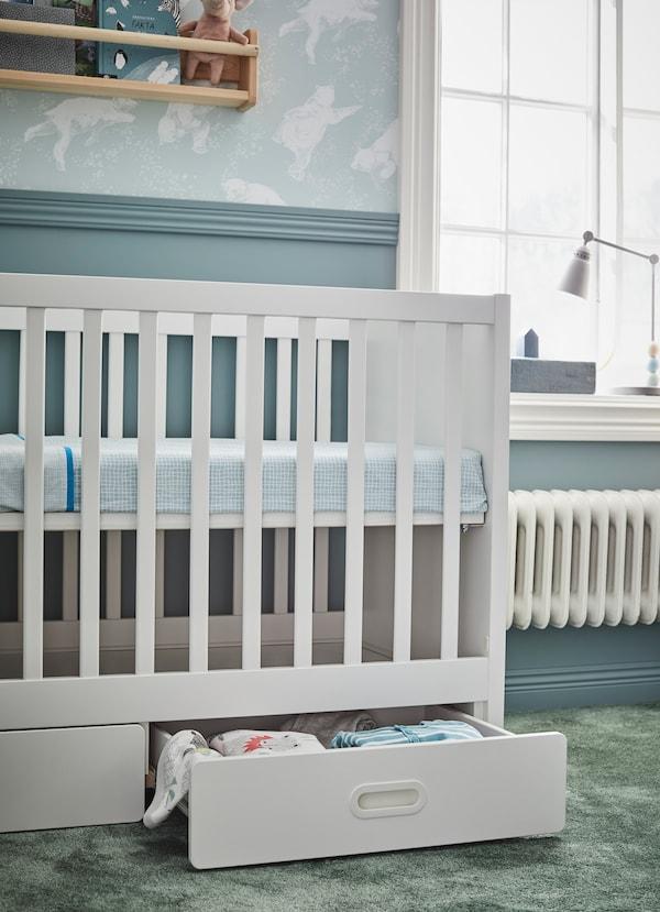 سرير أطفال أبيض STUVA FRITIDS من ايكيا في الوضع المرتفع. الرف الأبيض السفلي يحمل بطانيات ومفارش سرير الأطفال الرضع.
