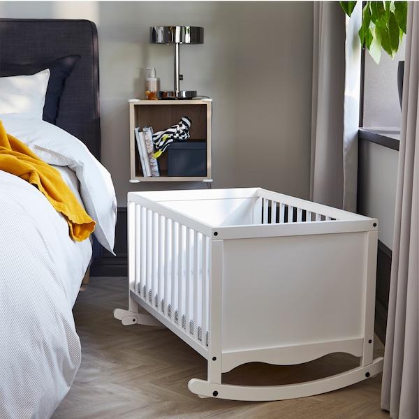 سرير أطفال رُضّع SOLGUL أبيض بجانب نافذة غرفة نوم وسرير طويل رمادي داكن مع منسوجات أسرة رمادية/مخططة وبطانية صفراء داكنة.