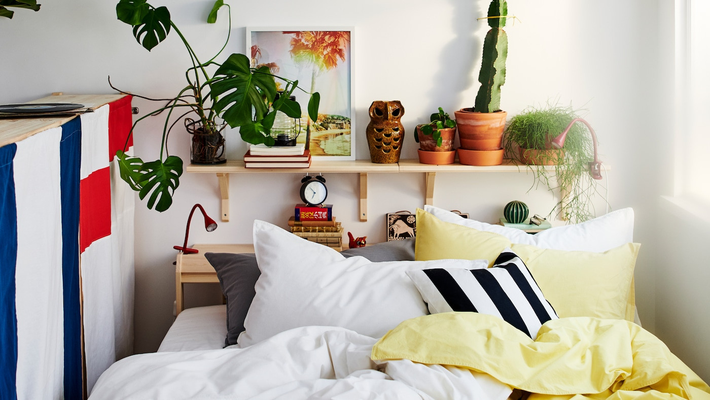 سرير بين نافذة وظهر وحدة تخزين مع الكثير من الوسائد وملاءات السرير باللون الأصفر والأبيض والأسود والرمادي.