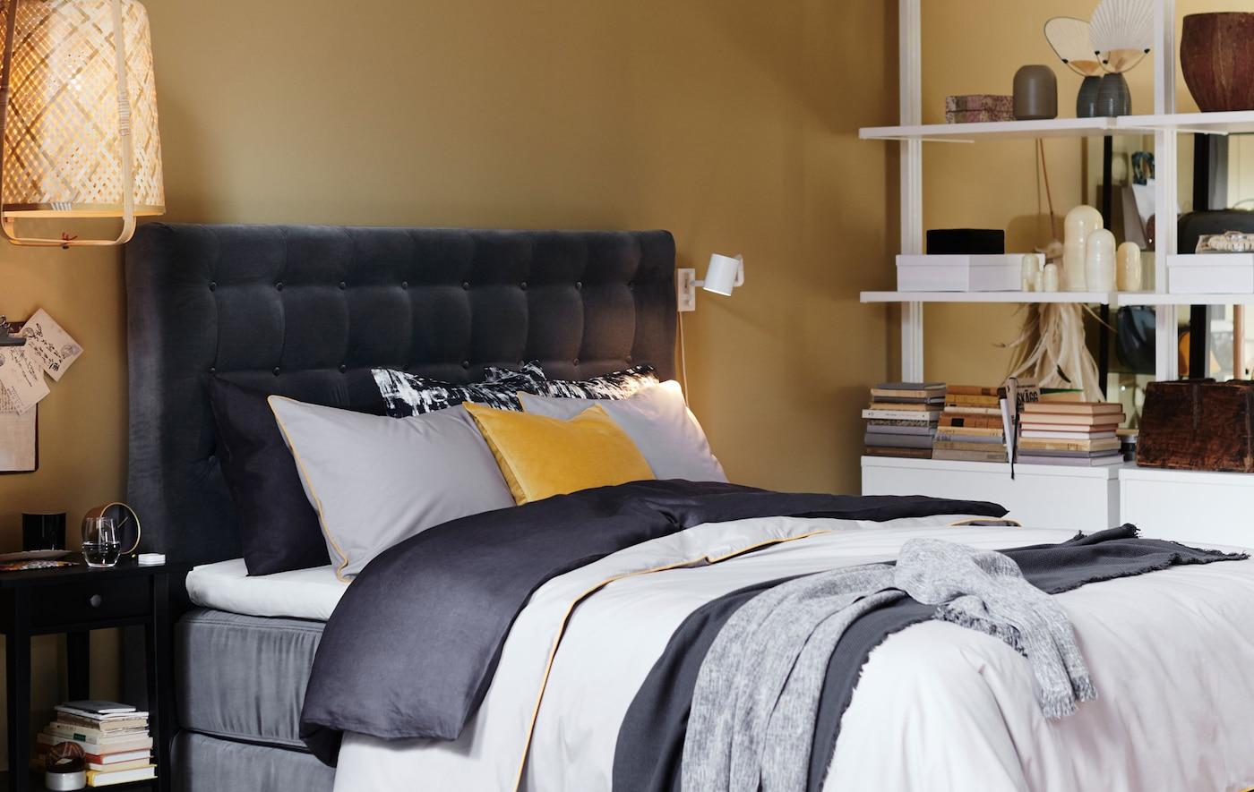 سرير مع لوح رأس مبطن مخملي رمادي ومفارش سرير في طبقات.