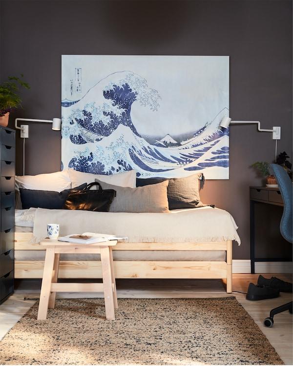 سرير من خشب الصنوبر ومقعد من خشب البتولا مع كتاب وكأس في الأمام، ولوحة كبيرة عليها موجة ومصباحان أبيضان مثبتان على الحائط.