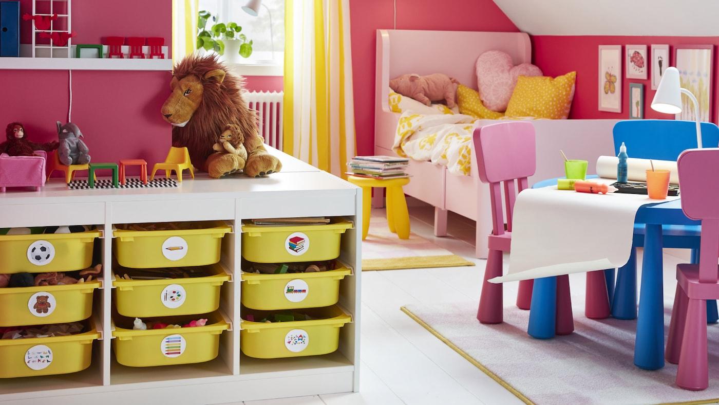 سرير قابل للتمديد BUSUNGE في زاوية بالقرب من طاولة وكراسي MAMMUT وتخزين TROFAST مع صناديق صفراء.