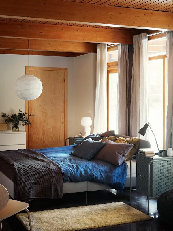سرير SLATTUM المنجد بأغطية زرقاءفي غرفة نوم حديثة مليئة بأشعة الشمس ومشرقة.