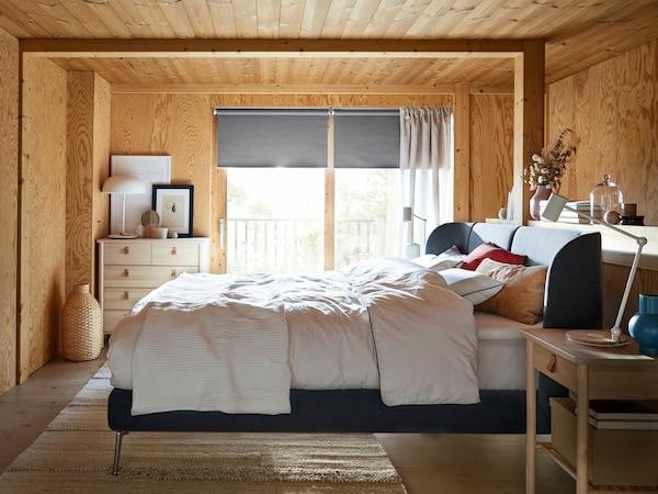 سرير TUFJORD أزرق في غرفة ذات ألواح خشبية، بينما يتدفق الضوء عبر النافذة خلفه.