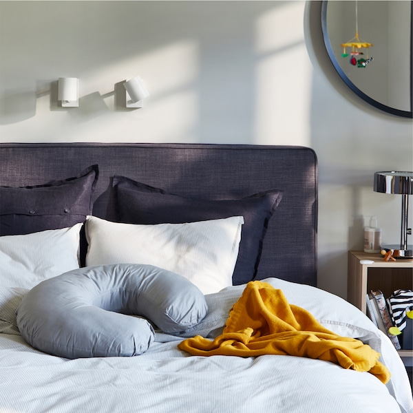 سرير طويل رمادي داكن مع منسوجات أسرّة رمادية/مخططة ورمادية داكنة، وبطانية صفراء داكنة ووسادة LEN للرضاعة باللون الرمادي.