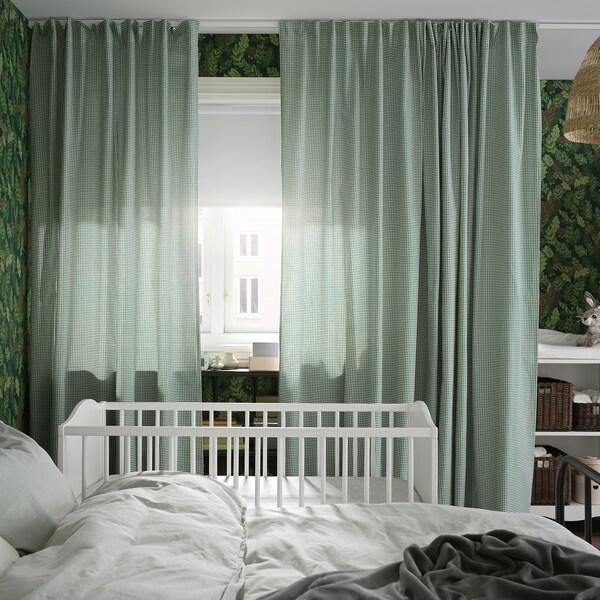 سرير وسرير أطفال بجوار نافذة مع ستائر أخضر/أبيض، وستارة لفافة معتمة بيضاء تغطي نصف النافذة.