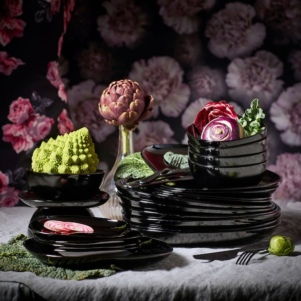 Stacked black dinnerware with flowers.