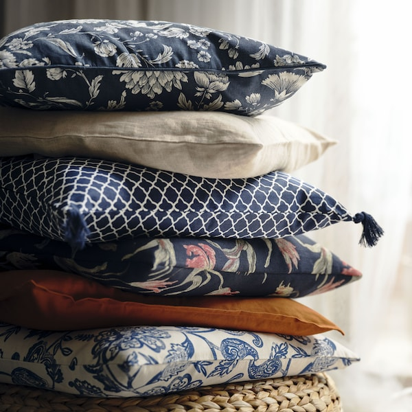 Stacked cushions, among them one with an IDALINNEA cover, on an ALSEDA banana-fibre stool standing on a multicolour rug.