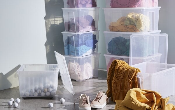 Stacked SAMLA plastic storage boxes of colour-coded clothes in the corner of a room with clothing strewn on the floor.