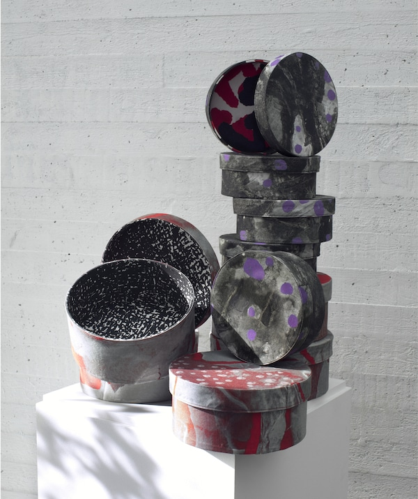 Stacks of patterned grey, purple and red boxes from the IKEA ANNANSTANS collection in different sizes with lids.