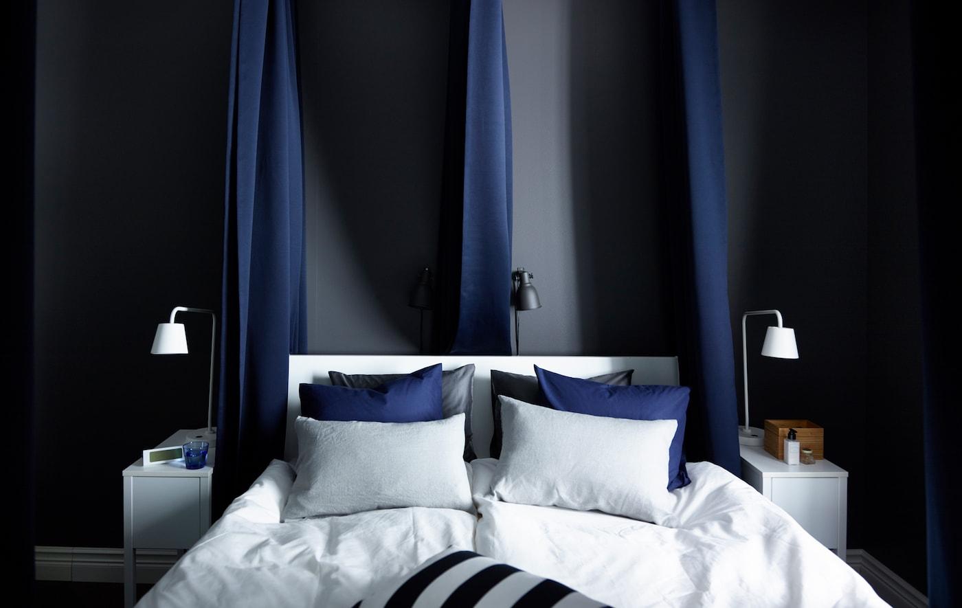 ستائر مبطّنة، لون أزرق داكن معلقة حول السرير من الخارج وفي المنتصف تساعد في حجب الصوت والضوء. حوائط داكنة وشراشف سرير بيضاء ناصعة تساعد في إضفاء إحساس بالهدوء.