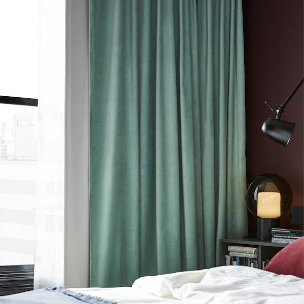 ستائر مُظلمة للغرف باللون الأخضر الفاتح، ومصباح حائط أسود، وغطاء وسادة أحمر داكن وغطاء لحاف أبيض.