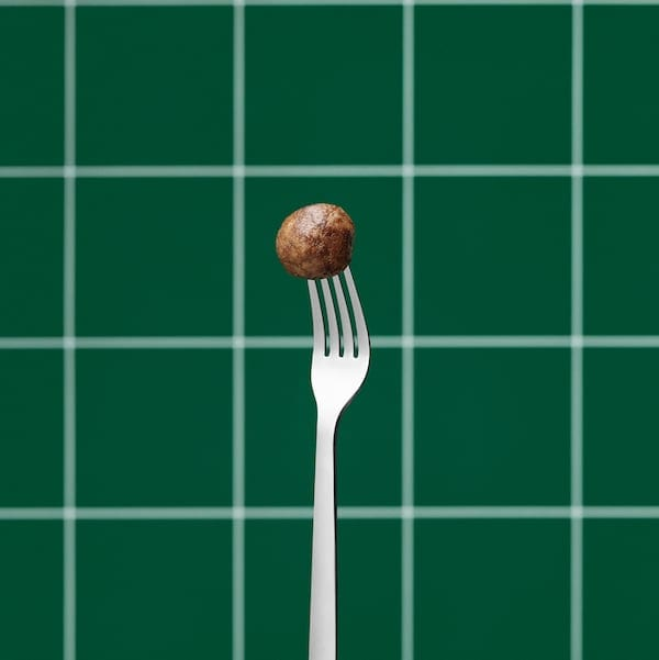 Stainless steel fork held upright, its tines stuck into a single plant ball. Green, tiled wall in the background.