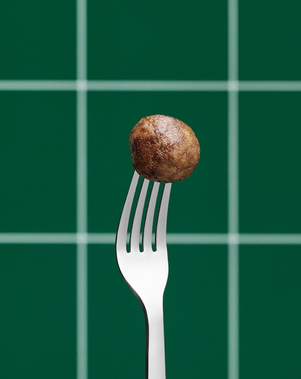 Stainless steel fork held upright, its tines stuck into a single plant-based meatball. Green, tiled wall in the background.