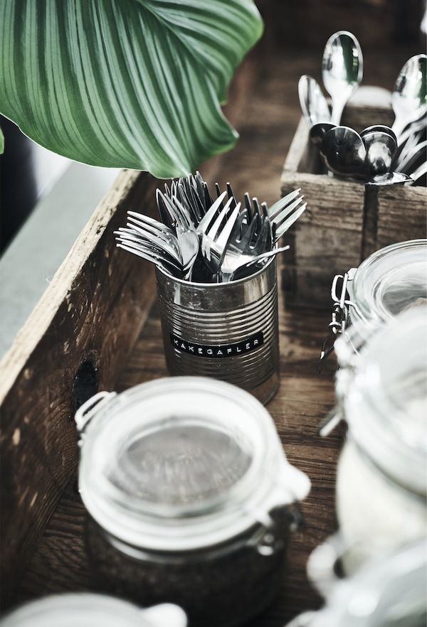 Stainless steel forks stored in a metal can.