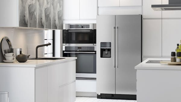 Stainless steel oven, microwave and refrigerator in a white and grey kitchen.