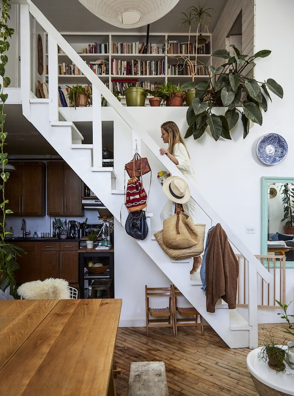 Staircase with plants and a table on the foreground.