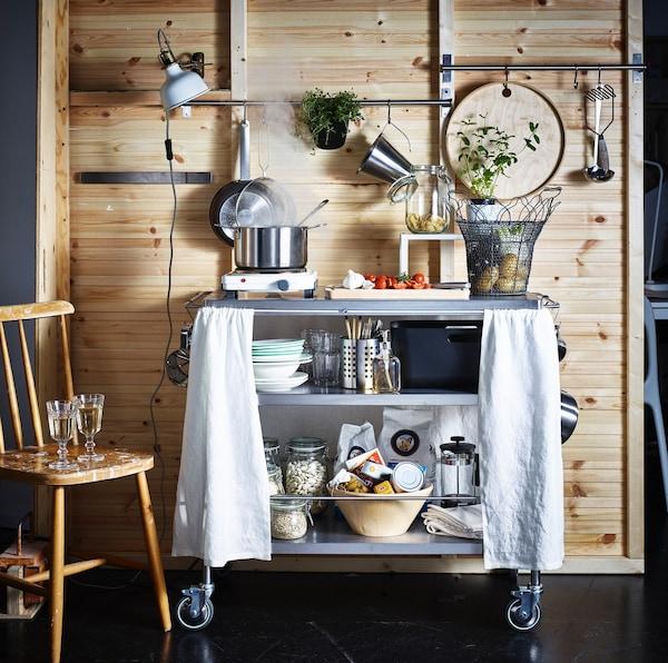 Stalowy barek kuchenny FLYTTA stojący w kuchni pod ścianą z desek.