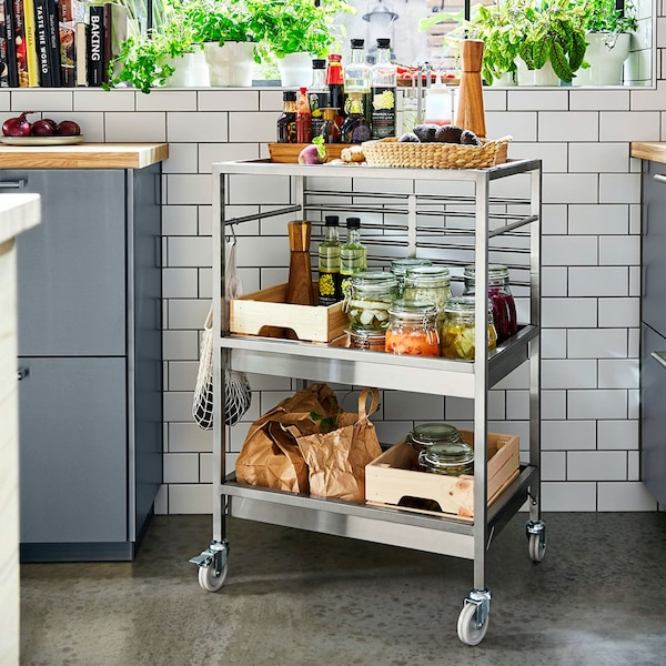Stalowy barek kuchenny z serii KUNGSFORS stojący w kuchni z białymi płytkami na ścianie.