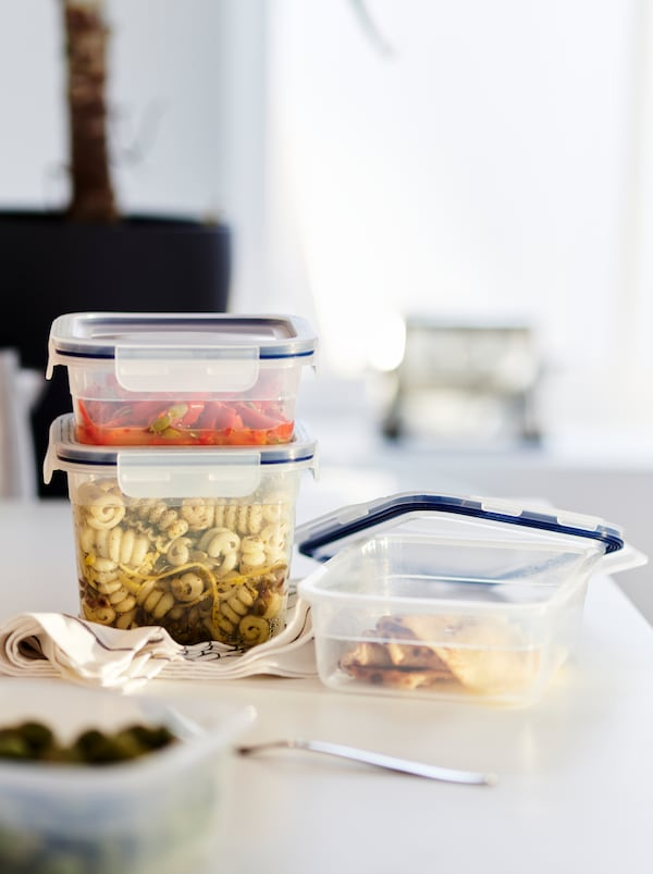 Standing on a worktop are different-size, stacked IKEA 365+ food containers with various blends of pasta and vegetables.