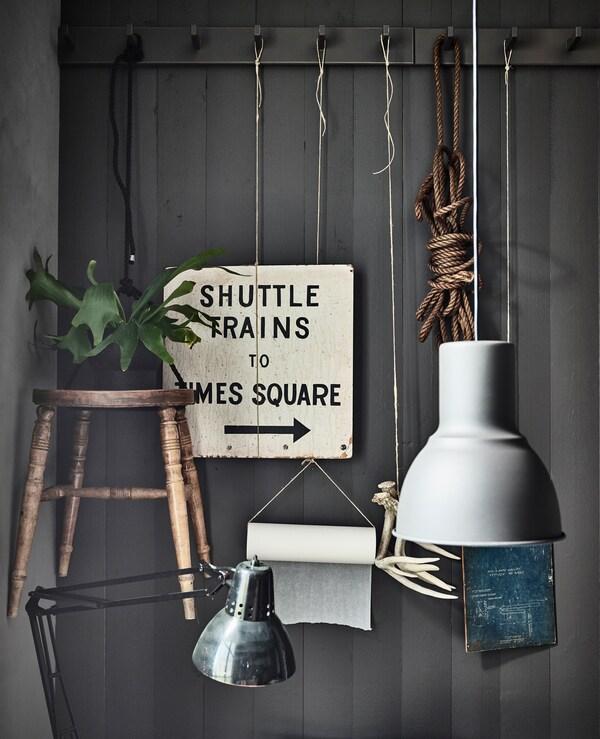 Stang på væggen med kroge og personlige ting, som skilte og planter, hænger til pynt i et køkken