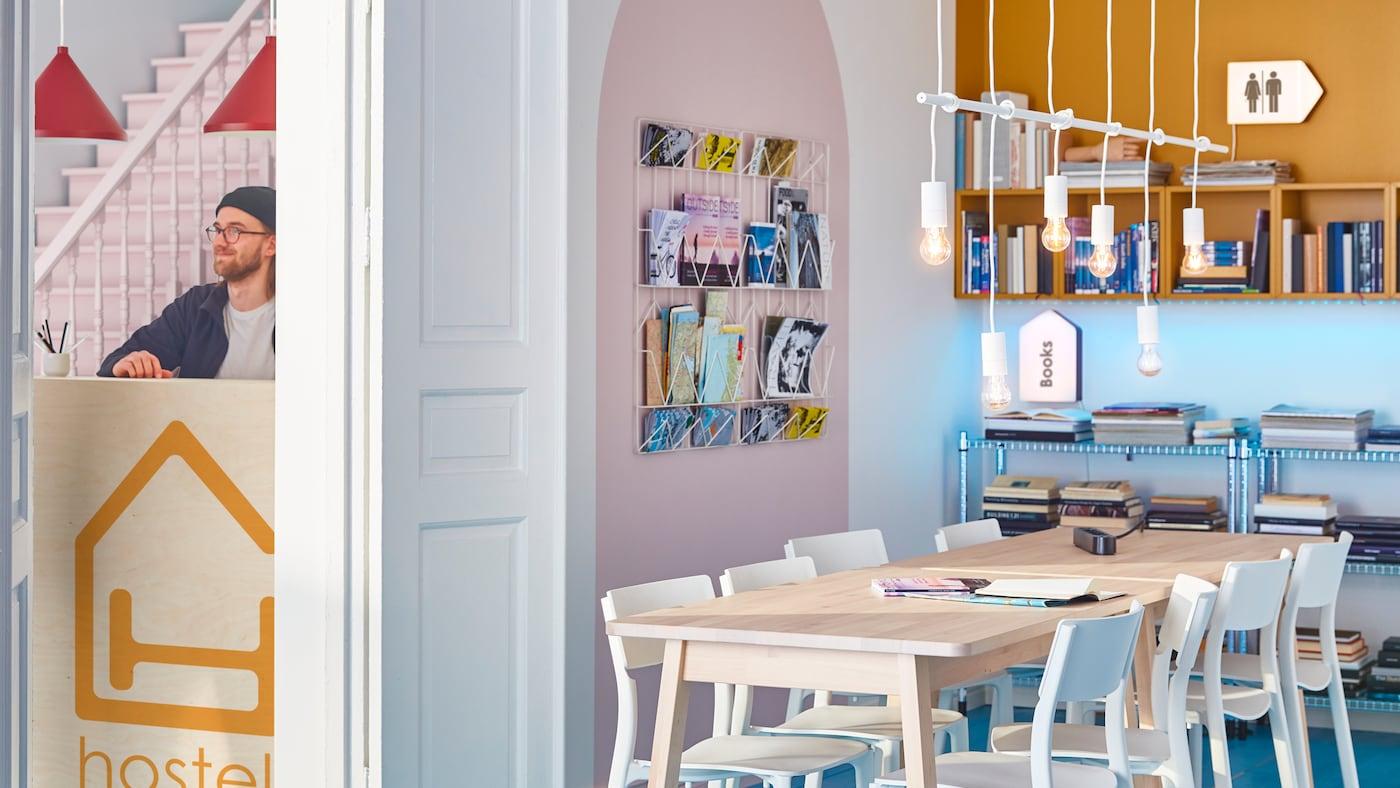 Stanza con grande tavolo in legno e sedie bianche al centro, mobili a parete con riviste e libri.