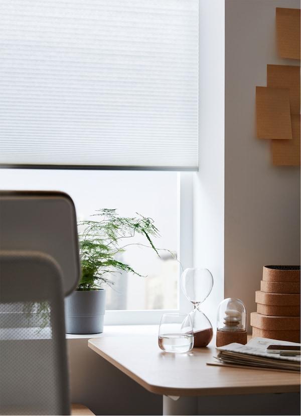 ستارة عاتمة HOPPVALS من ايكيا، على شكل خلية نحل، على نافذة، خلف مكتب عمل وكرسي.