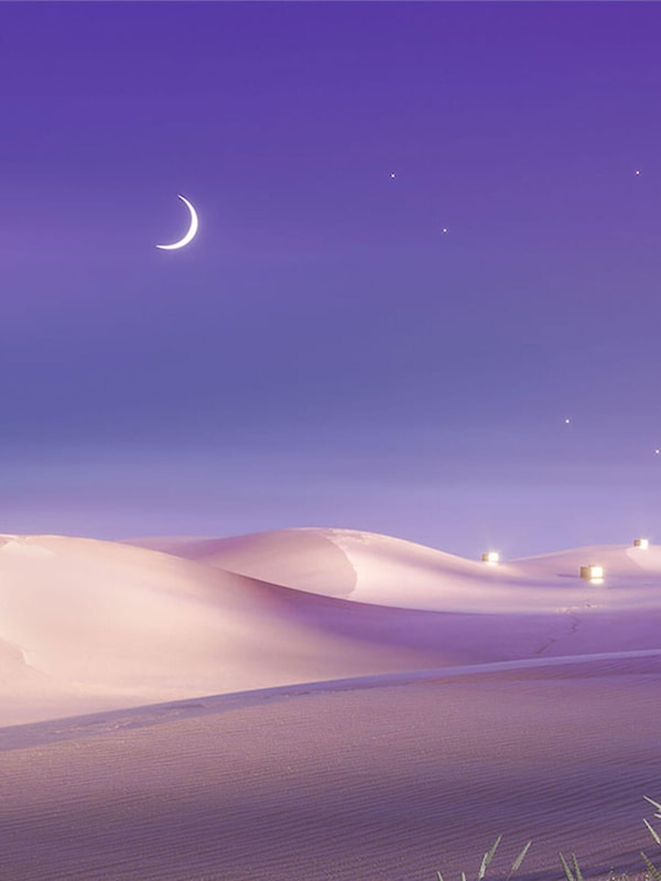 Stars and a crescent moon in a violet-coloured night sky above sand dunes in a desert landscape.