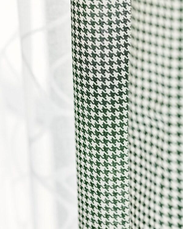 ستارتانمن القماش معلقةجنبًا إلى جنب، واحدة من قماشقطن أبيض شفاف، وواحدة أخضروأبيض مربعات.