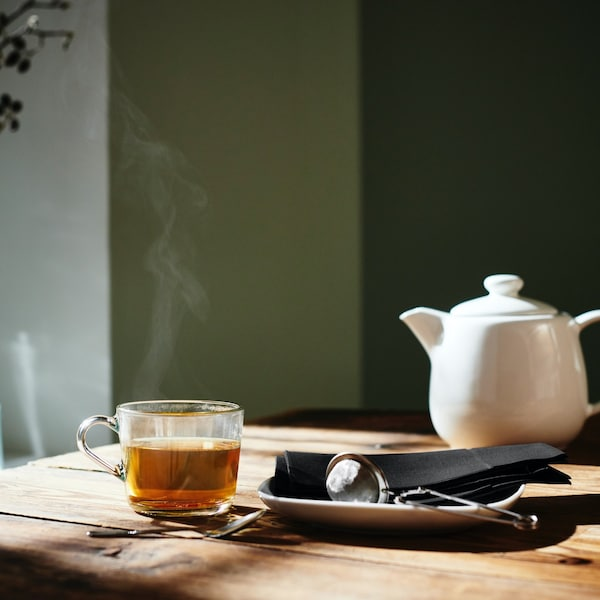 Steaming tea cup and a teapot