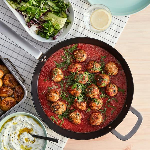 Stekepanne med planteboller laget av VÄRLDSKLOK plantebasert hakk i tomatsaus og ei ildfast form med ovnsstekte poteter.