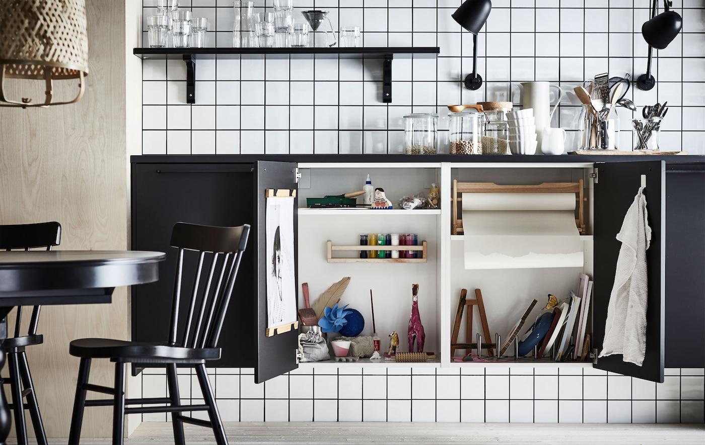 سطح عمل مطبخ مع اثنين من أبواب الخزائن مفتوحين في الأسفل، يكشفان عن استوديو فن كامل مصغر مخبأ في الداخل.