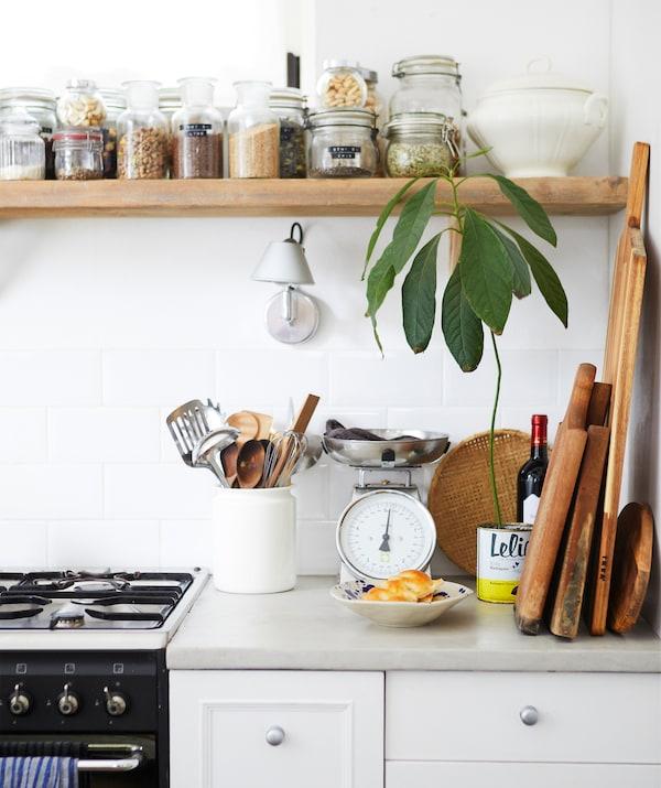 سطح عمل مطبخ مع موقد وألواح خشبية، ومرطبانات من المكونات الجافة على رف خشبي من أعلى.